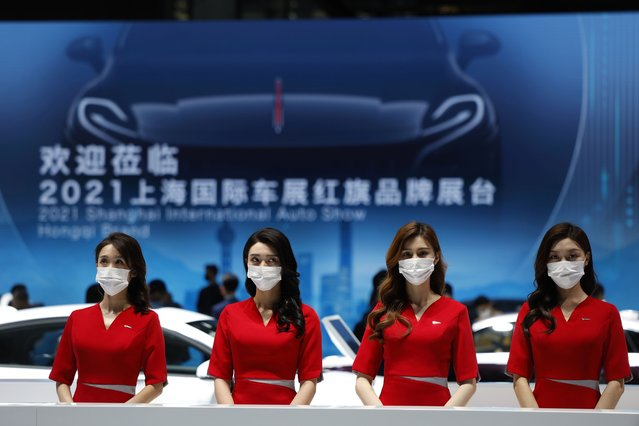Receptionists wait for visitors at the booth for Chinese luxury auto brand Hongqi at the Shanghai Auto Show in Shanghai on Tuesday, April 20, 2021. Automakers are looking to China, the biggest auto market by sales volume and the first major economy to rebound from the pandemic, to propel a revival in demand and reverse multibillion-dollar losses. (Photo by Ng Han Guan/AP Photo)