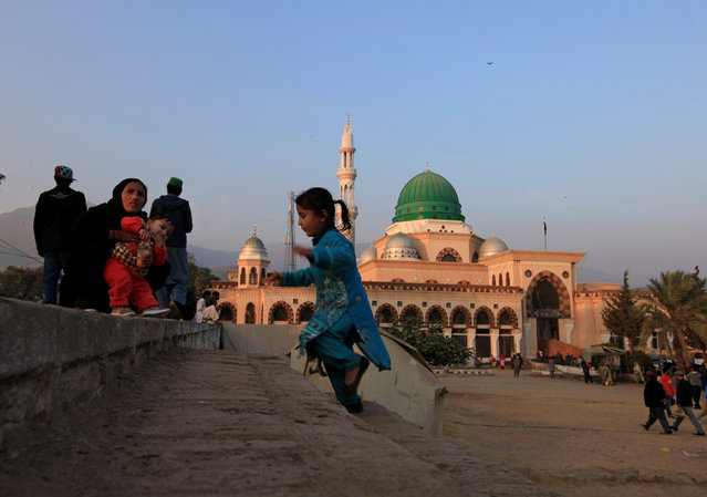 A girl plays near her mother as they're visiting the shrine of Bari Imam in Islamabad, Pakistan December 2, 2016. (Photo by Faisal Mahmood/Reuters)