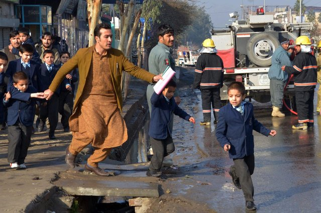 An Afghan teacher, in brown, helps school children run from the site of clashes near the Pakistan consulate in Jalalabad, capital of Nangarhar province, Afghanistan, Wednesday, January 13, 2016. Several members of the Afghan security forces were killed Wednesday after unidentified gunmen attacked the Pakistani consulate in a volatile eastern province, an official said on Wednesday. (Photo by Mohammad Anwar Danishyar/AP Photos)