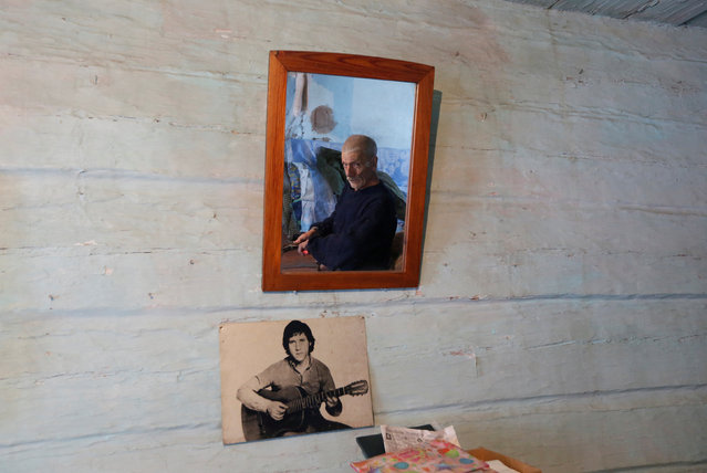 Mikhail Baburin, 66, is reflected in a mirror next to a portrait of Soviet singer, poet and actor Vladimir Vysotsky while he makes a broom at his house in the remote Siberian village of Mikhailovka, Krasnoyarsk region, Russia, December 5, 2016. (Photo by Ilya Naymushin/Reuters)