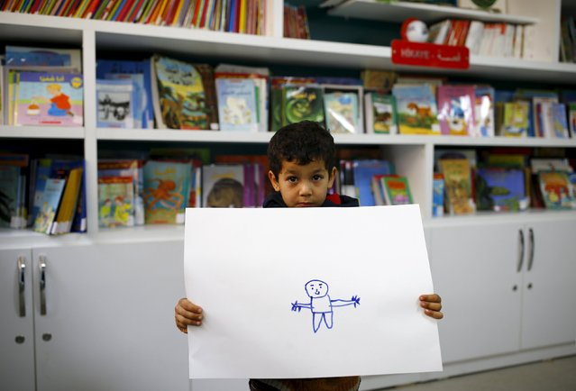 "Syrian refugee boy Gays Cardak, 6, shows his drawing in a school library in the Yayladagi refugee camp in Hatay province near the Turkish-Syrian border, Turkey, December 16, 2015. ""I'm going to be a doctor and an engineer. We the engineers will rebuild Syria, and I'll take the (soldiers) to hospital"", Cardak said. (Photo by Umit Bektas/Reuters)"