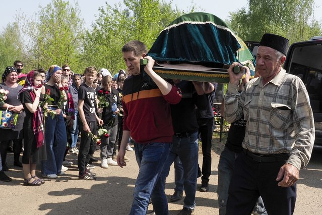 Men carry a coffin with the body of Elvira Ignatieva, an English language teacher, in Kazan, Russia, Wednesday, May 12, 2021, who was killed in a shooting at a school on Tuesday. Russian officials say a gunman attacked a school in the city of Kazan and Russian officials say several people have been killed. Officials said the dead in Tuesday's shooting include students, a teacher and a school worker. Authorities also say over 20 others have been hospitalised with wounds. (Photo by Dmitri Lovetsky/AP Photo)