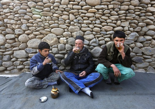 Afghan laborers drink tea at a tea shop along a street on the outskirts of Kabul, January 26, 2015. (Photo by Omar Sobhani/Reuters)