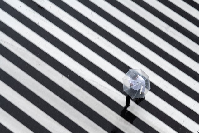 A pedestrian crosses a street on a rainy day in Tokyo on May 13, 2021. (Photo by Charly Triballeau/AFP Photo)