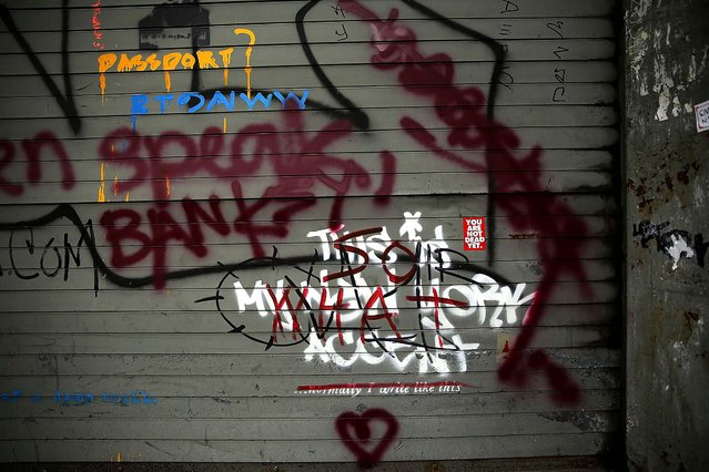 "Banksy's work, ""This is My New York Accent"", is seen on October 3, 2013 after being vandalized by other graffiti. (Photo by Spencer Platt/Getty Images)"