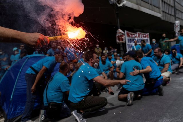 A man holds a flare as workers of a fertiliser company shout slogans during a demonstration against a planned labour bill, during a 24-hour strike in Athens, Greece, June 10, 2021. Widespread strikes in Greece brought public transport and other services to a halt Thursday, as the country's largest labor unions protested against employment reforms they argue will make flexible workplace changes introduced during the pandemic more permanent. (Photo by Alkis Konstantinidis/Reuters)