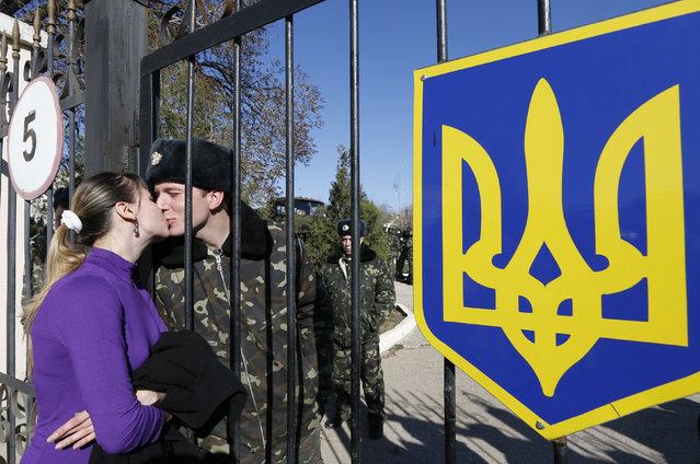 A woman kisses a Ukrainian serviceman through the gate as he stands on the territory of a military unit located in the village of Lyubimovka near a local airfield, southwest of the capital Simferopol March 3, 2014. (Photo by Vasily Fedosenko/Reuters)