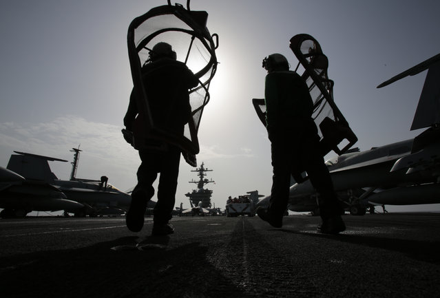 U.S. sailors carry equipment on the flight deck of the USS Carl Vinson aircraft carrier in the Persian Gulf, Thursday, March 19, 2015. (Photo by Hasan Jamali/AP Photo)