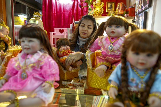 "A ""child angel"" doll owner, Supattar Wichainan, 27, decorates her ""child angel"" dolls at her shop inside a department store in Bangkok, Thailand, January 26, 2016. (Photo by Athit Perawongmetha/Reuters)"