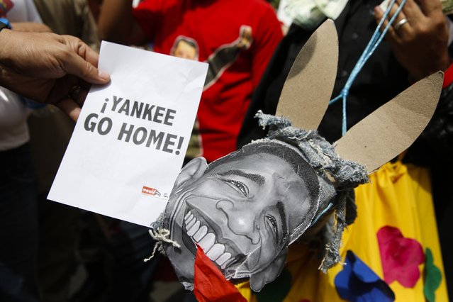 "Supporters of Venezuela's President Nicolas Maduro hold a placard depicting U.S. President Barack Obama during a rally against imperialism, in Caracas March 15, 2015. Venezuela's parliament granted President Maduro decree powers on Sunday for the rest of 2015 in a move he says is to defend the country from U.S. meddling but opponents decry as evidence of autocracy. The placard reads, ""Yankee go home"". (Photo by Carlos Garcia Rawlins/Reuters)"