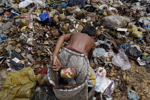 Seu, a 13-year-old boy who makes 25 US cents per day, collects beer cans at dumpsite outside Siem Reap March 19, 2015. (Photo by Athit Perawongmetha/Reuters)