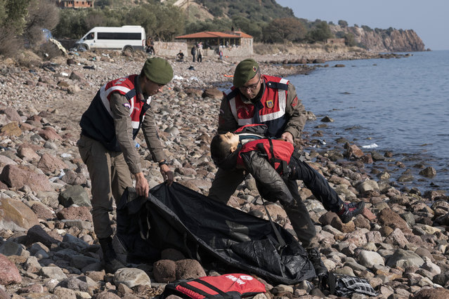 A Turkish paramilitary police officer holds the lifeless body of a migrant boy near the Aegean town of Ayvacik, Canakkale, Turkey, Saturday, January 30, 2016. A boat carrying migrants to Greece hit rocks off the Turkish coast on Saturday and capsized, killing at least 37 people, including five children, officials and news reports said. Some 75 other migrants were rescued. A Turkish government official said he expects the death toll from the incident to rise as rescue workers try to reach other migrants believed trapped inside the wreckage of the boat which sank shortly after departing from the Aegean resort of Ayvacik. (Photo by Halit Onur Sandal/AP Photo)