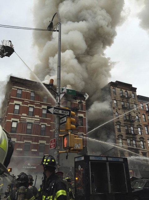 Fire officials are seen outside a building which collapsed and burst into flames at Second Avenue and East 7th Street in New York's East Village in this picture courtesy of Andrea Scarantino taken March 26, 2015. (Photo by Andrea Scarantino/Reuters)