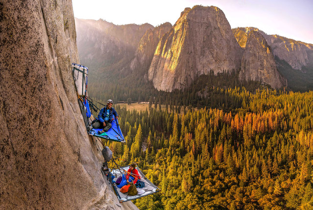 Morgane Choquet and Samuel Cobb relax in a vertical campsite on the slopes of El Capitan, Yosemite National Park. (Photo by Alexandre Eggermont/Caters News)