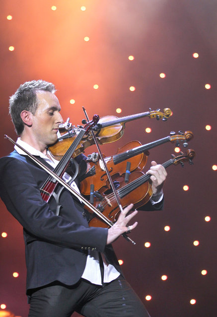 Ukrainian violinist Oleksandr Bozhyk plays four violins as he attempts to establish a new Guinness world record, organizers said, in Lviv December 8, 2012. (Photo by Marian Striltsiv/Reuters)