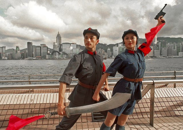 In this Tuesday, July 21, 1998, file photo, dancers of China's National Ballet, Sun Jie, left, and Zou Zhi Rui, dressed in military uniforms pose for photographers at Hong Kong's waterfront. A year after Beijing imposed a harsh national security law on Hong Kong, the civil liberties that raised hopes for more democracy are fading. (Photo by Vincent Yu/AP Photo/File)