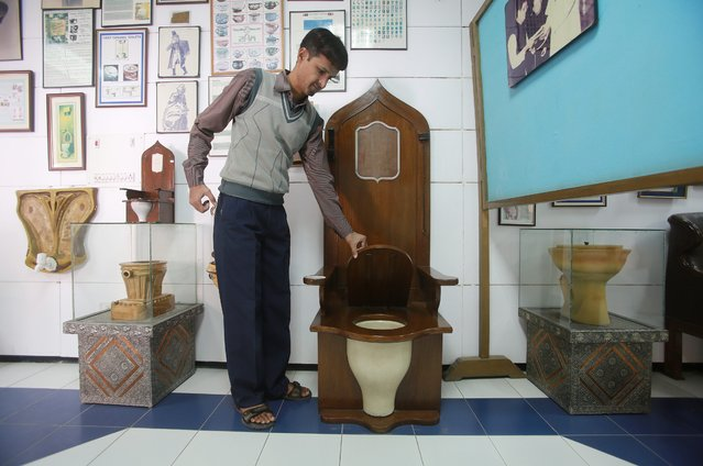 An attendant shows a replica of a 'rumble throne' of a French monarch, displayed at the Sulabh international toilet museum in New Delhi, India, 19 November 2013. The museum traces the 5,000 year history of toilets and aims to educate people about the health and social aspects of sanitation. November 19 is marked as the World Toilet Day. (Photo by Money Sharma/EPA)