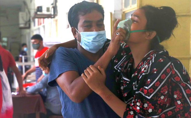A man assists a patient facing difficulties in breathing at the Medical College Hospital in Rajshahi, 254 kilometers (158 miles) north of the capital, Dhaka, Bangladesh, June 16, 2021. (Photo by Kabir Tuhin/AP Photo)