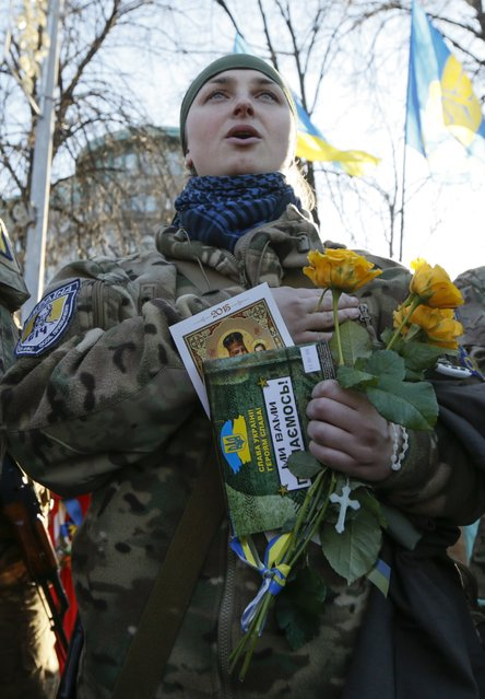 """A new volunteer of the Ukrainian interior ministry's special battalion """"Sich"""" takes an oath of allegiance to the country during a ceremony in Kiev March 16, 2015. According to the battalion's commander, the volunteers will be headed to the frontlines in Eastern Ukraine, shortly after their ceremony. (Photo by Valentyn Ogirenko/Reuters)"""