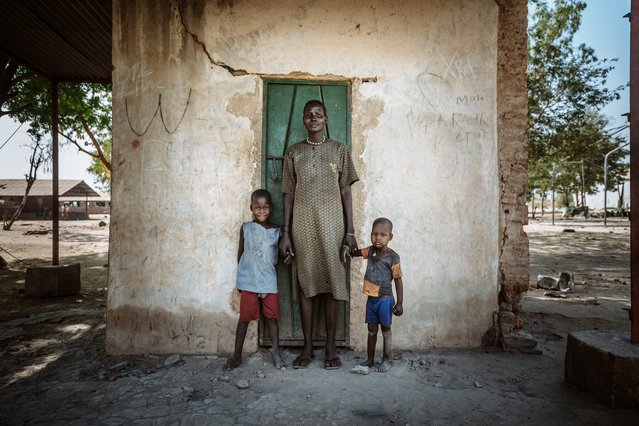 A woman stands with her two children outside a square building in Bentiu Town, South Sudan. Formerly attached to a larger building, the square room, which is all that remains now, is where this young family has been living for the past six months. (Photo by Muse Mohammed/IOM)