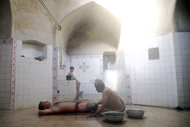 In this November 21, 2014 photo, bathhouse worker Ali Tayyeb, 70, scrubs a man to remove dead skin after sitting in a steamy room at a bathhouse in Yazd, Iran. (Photo by Ebrahim Noroozi/AP Photo)