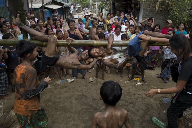 Youths play a traditional pillow fight game on a bamboo pole during festivities marking the 69th anniversary of Myanmar Independence Day on the outskirts of Yangon on January 4, 2017. Various traditional and local events were held on the holiday which marks the 69th anniversary of the country known before as Burma when British colonial rule ended on January 4, 1948. (Photo by Ye Aung Thu/AFP Photo)