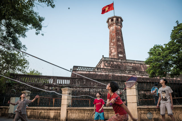 """""""Sports Stars"""". In Lenin Park, set against the backdrop of Cột cờ Hà Nội (Hanoi Flag Tower) which forms part of the Hanoi Citadel, Vietnamese children sparring in a game of badminton. On the weekends, Lenin Park become makeshift sporting grounds for badminton and futsal for both the young and old. This is symbolic of the freedom enjoyed by the locals of modern Vietnam post Soviet style communism of the 80s. Photo location: Hanoi, Vietnam. (Photo and caption by Justin Tiew/National Geographic Photo Contest)"""