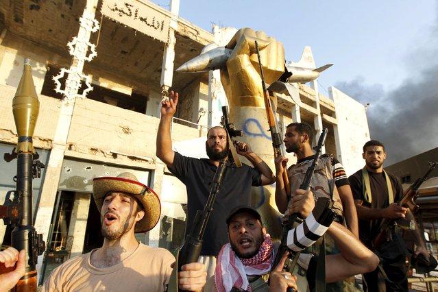 Libyan rebels celebrate after taking Libyan leader Muammar Gaddafi's Tripoli bastion, the Bab Al-Aziziya compound, August 23, 2011. (Photo by Louafi Larbi/Reuters)