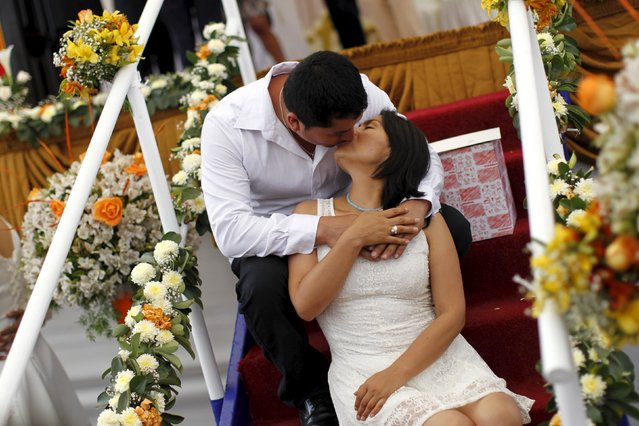 A couple kiss while posing for a picture after a mass wedding ceremony ahead of Valentine's Day celebration in Lima, Peru, February 12, 2016. (Photo by Janine Costa/Reuters)