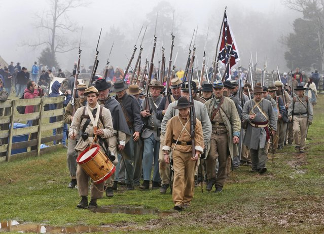 Confederate re-enactors march back to camp after a re-enactment of the Battle of Appomattox Court House as part of the commemoration of the 150th anniversary of the surrender of the Army of Northern Virginia at Appomattox Court House in Appomattox, Va., Thursday, April 9, 2015. (Photo by Steve Helber/AP Photo)