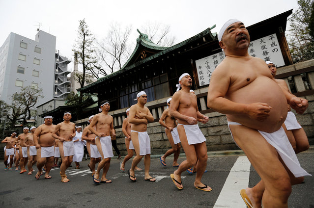 """Men wearing the traditional """"fundoshi"""" or loin cloth run to warm up before bathing in ice-cold water outside the Teppozu Inari shrine in Tokyo, Japan, January 8, 2017. (Photo by Toru Hanai/Reuters)"""