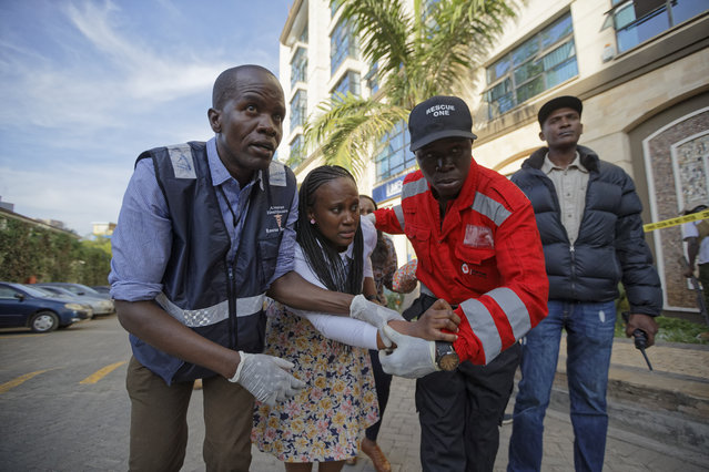 A civilian is helped by paramedics at a hotel complex in Nairobi, Kenya Tuesday, January 15, 2019. Terrorists attacked an upscale hotel complex in Kenya's capital Tuesday, sending people fleeing in panic as explosions and heavy gunfire reverberated through the neighborhood. (Photo by Ben Curtis/AP Photo)