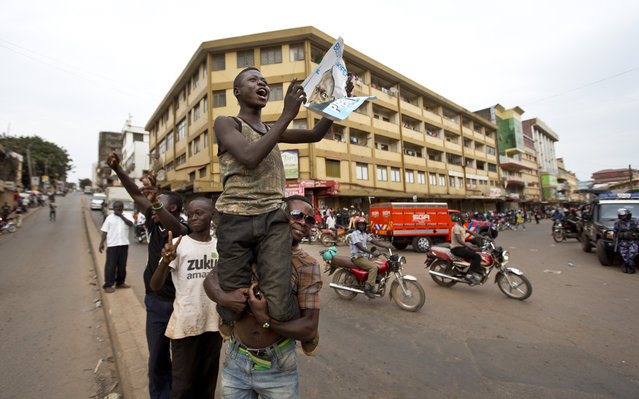 An opposition supporter holds up a poster of opposition candidate Kizza Besigye, who remains under house arrest, shortly after the election result was announced, in downtown Kampala, Uganda, Saturday, February 20, 2016. (Photo by Ben Curtis/AP Photo)