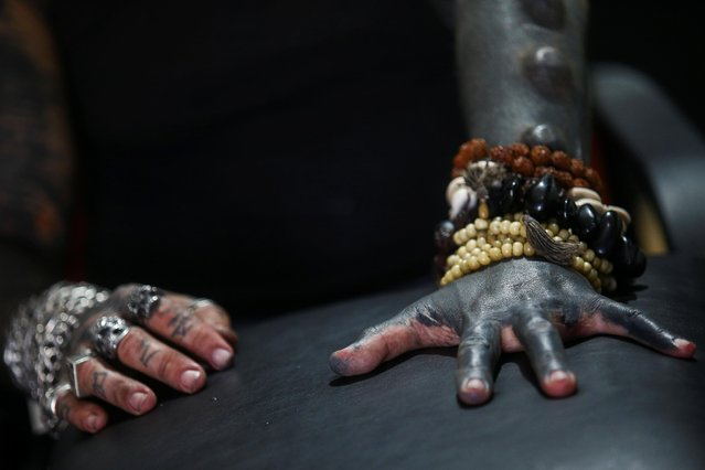 Brazilian tattoo artist Michel Praddo, also known as Diabao or Human Satan, who cut off a finger as part of his body modifications, shows his hands in Praia Grande, Brazil on August 18, 2021. (Photo by Carla Carniel/Reuters)