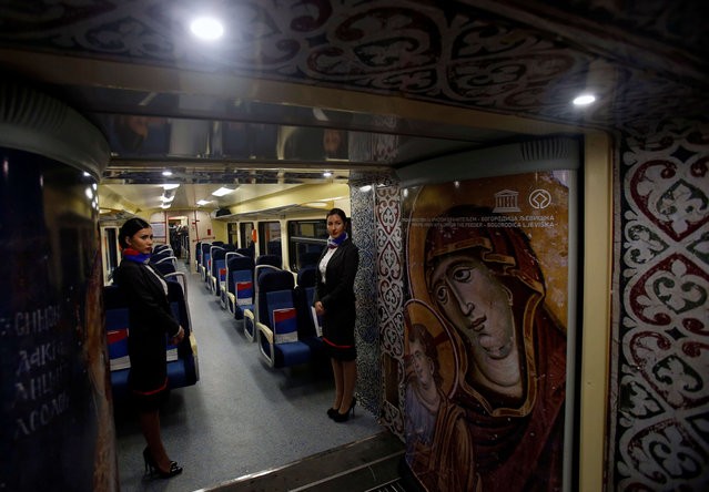 Train hostesses stand in a train carriage decorated with iconic religious figures as it departs from Belgrade to Mitrovica, Kosovo at Belgrade's railway station, Serbia, Saturday, January 14, 2017. (Photo by Darko Vojinovic/AP Photo)