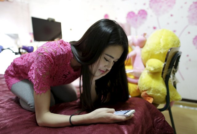 Online hostess Xianggong checks her mobile phone as she sits on her bed after a live broadcast in Beijing, February 10, 2015. (Photo by Jason Lee/Reuters)