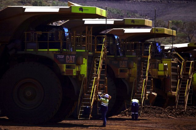 Workers prepare giant mining trucks at the Fortescue Solomon iron ore mine located in the Sheila Valley, around 400 km (249 miles) south of Port Hedland, in the Pilbara region of Western Australia in this December 2, 2013 file photo. Fortescue Metals is expected to report H1 results this week. (Photo by David Gray/Reuters)