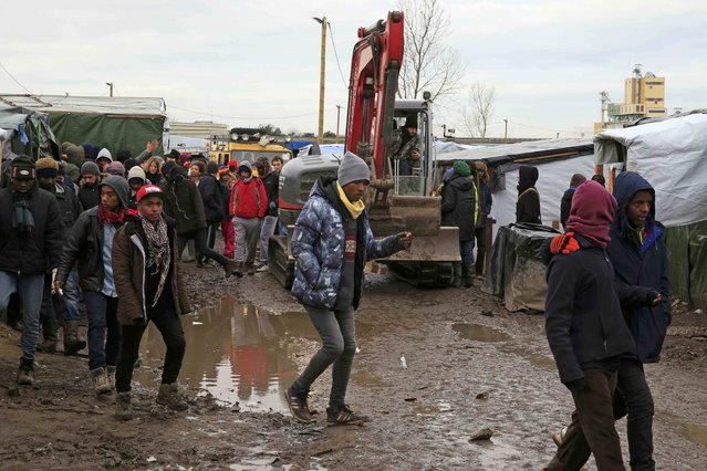 """Migrants walk in the mud near a crane operated by volunteers that makes its way along a path in the southern part of a camp for migrants called the """"jungle"""", in Calais, northern France, February 23, 2016. (Photo by Pascal Rossignol/Reuters)"""