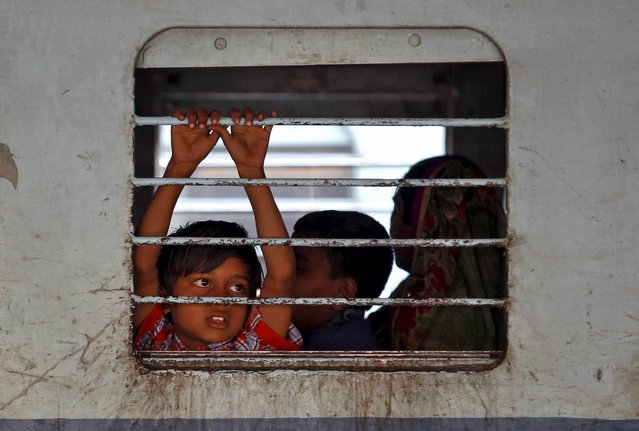 A girl looks out from inside a coach of a stationed passenger train at a railway station in Ahmedabad, India, February 25, 2016. (Photo by Amit Dave/Reuters)