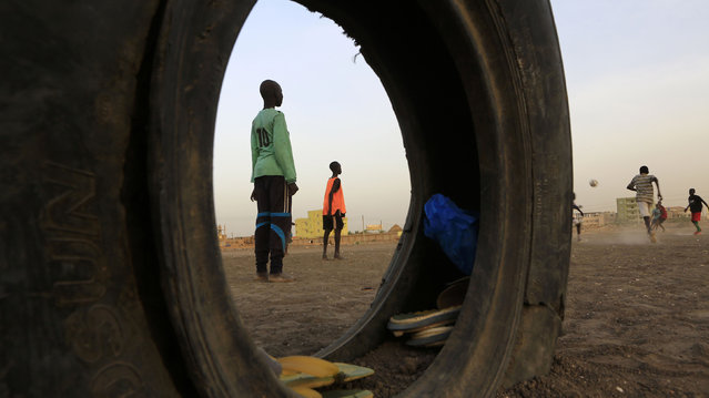 Boys are pictured through a tire as they play soccer at a railway station camp, where refugees from South Sudan have stayed for four years, in Khartoum May 11, 2014. (Photo by Mohamed Nureldin Abdallah/Reuters)