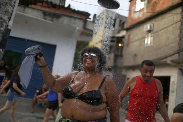 "A reveller refreshes herself with a shower during the annual ""Se Benze que da"" block party, created by late councilwoman Marielle Franco, in the Mare slum in Rio de Janeiro, Brazil on February 23, 2019. (Photo by Pilar Olivares/Reuters)"