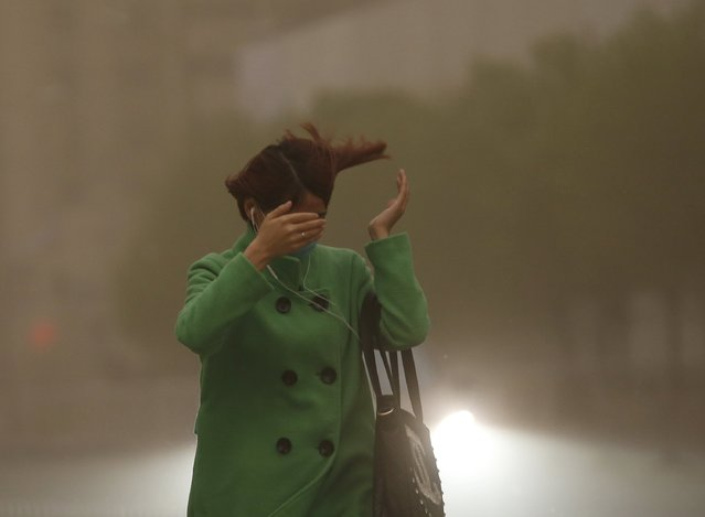 A woman reacts as she walks in a sand storm in Beijing on April 15, 2015. A heavy sand storm is reported to have swept through 11 provinces in northern China on Wednesday. Beijing Meteorological Bureau has issued a yellow alert for the storm, People's Daily reported. (Photo by Reuters/China Daily)