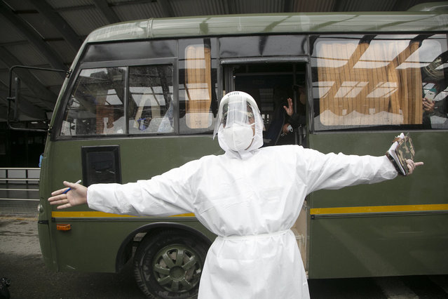 A Nepalese army man in protective gear gestures to show the bus waiting for Nepalese people evacuated from Afghanistan as they arrive via Kuwait at the Tribhuvan International Airport in Kathmandu, Nepal, Tuesday, August 17, 2021. (Photo by Niranjan Shrestha/AP Photo)