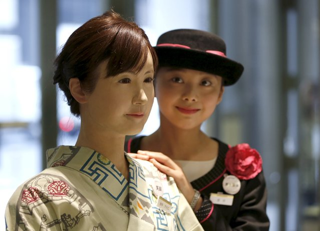 A reception employee of Nihonbashi Mitsukoshi department store (R) poses for a photo with a kimono-clad android robot named Aiko Chihira, developed by Toshiba Corp., during its unveiling at the reception desk of the store in Tokyo April 20, 2015. (Photo by Issei Kato/Reuters)