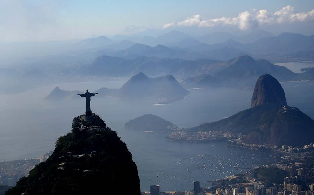 The Christ the Redeemer statue stands above Rio de Janeiro on June 19, 2013.  Sugar Loaf mountain is at right. (Photo by Renata Britto/Associated Press)