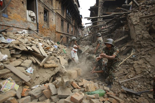 Rescue workers remove debris as they search for victims of earthquake in Bhaktapur near Kathmandu, Nepal, Sunday, April 26, 2015. (Photo by Niranjan Shrestha/AP Photo)