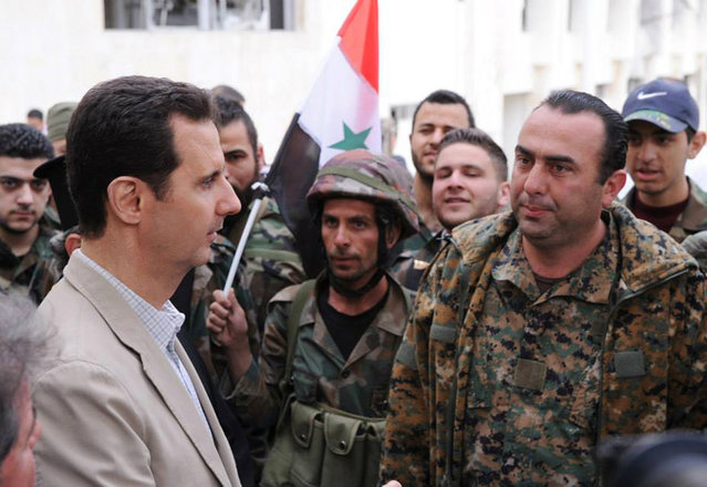 In this file photo taken on Sunday April 20, 2014 and released by the Syrian official news agency SANA, Syrian President Bashar Assad, left, talks to government soldiers during his visit to the Christian village of Maaloula, near Damascus, Syria. (Photo by SANA via AP Photo)