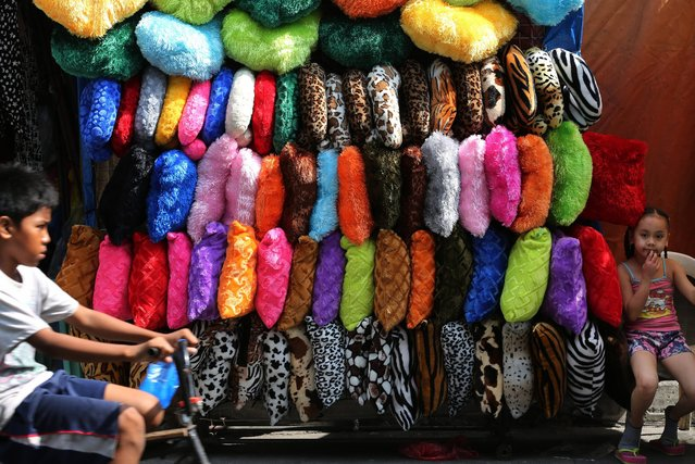 A Filipino girl sits beside pillows for sale along a street in Manila, Philippines, Tuesday, March 8, 2016  (Photo by Aaron Favila/AP Photo)