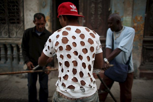 Plumber Lidil Horstmann (C), 26, wears a t-shirt that he cut up with holes which he said helps ventilates against high temperatures as he works on the street in downtown Havana, February 25, 2016. (Photo by Alexandre Meneghini/Reuters)