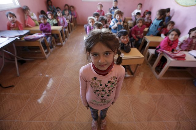 Five-year-old Razan Nader poses inside a classroom in the rebel-controlled area of Maarshureen village in Idlib province, Syria March 12, 2016. (Photo by Khalil Ashawi/Reuters)